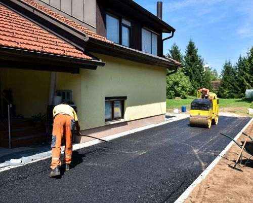 contractors are working driveway paving with asphalt